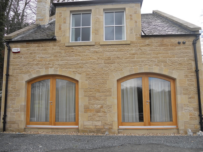 Stone extension with curved oak doors and dormer roof